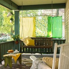 vintage scarfs used as privacy screening on this cute porch... (hmmm--thinking maybe I could do something with sheets for my front porch!)