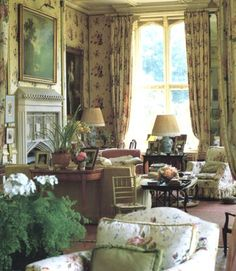 wall fabric and curtains match table has a plant, photos, a small silver vase with cut flowers