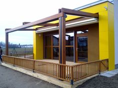 Pergole din lemn Elite, pergole pavilion Gibus cu structura lemn, acoperis retractabil si sistem de drenare integrat in profile pentru terase. Pergole paviliom de exceptie pentru terase la un pret excelent. Foto terasa galbena umbrita cu pergola Elite.