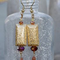 Beautiful matte gold plated textured rectangle beads with chinese and Swarovski crystals and Oregon sunstone bead dangles. Gold filled head pin and gold plated surgical steel ear wire. Just shy of 3 inches from top of ear wire to bottom of earring, Comes wrapped in tissue in a gift bag ready for ...