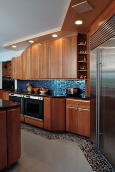A shimmering blue backsplash and mosaic tile floor accent brings a Mediterranean flair into this contemporary kitchen. The stainless steel appliances are state-of-the-art and, along with black countertops, create a sleek and modern feel.