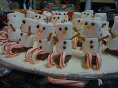 Marshmallow snowmen on candy cane and mini hershey bar sleds!  these lil guys are so cute!