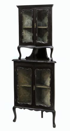 Victorian corner display cabinet, early 20th c., an ebonized finish with upper and lower two door shelved display areas separated by an open shelf, rising on cabriole legs with cuffed feet