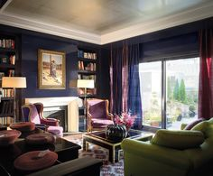 This living room is a deep purple color, accented with various shades of blues and aubergine. The area rug is vibrant and exciting.