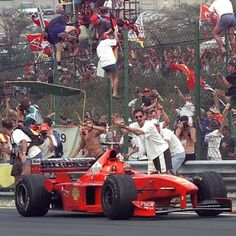 Germany's Michel Schumacher waves from his Ferrari at fans who invaded the track, with others climbing the wire fence during his victory lap, after he won the Hungarian Grand Prix near Budapest Sunday, August 16, 1998. Fans invaded the track while cars where still completing their last lap