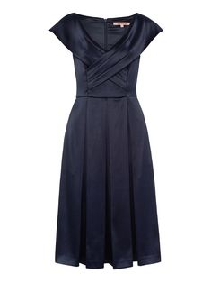 Sophisticated and seductive, our Biella Dress is a vision in silky navy, with an alluring sheen. The dress has cap sleeves, elegant detailing at the chest, and a fitted waist that gives to box pleats, resting at the knee. Lined for comfort and fitted with a concealed zipper at the back.