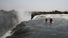 Tourists swim in the Devil's Pool on the edge of the Zambian side of Victoria Falls: Every year, during the dry season of September to December, the waterfall's flow of water is much lower than it is during full current. When the levels drop, a natural rock barrier comes close enough to the surface, allowing swimmers to frolic in relative safety up to a few inches away from the point where the water cascades over the falls.