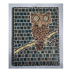 Mutli-brown owl mosaic with blue and brownish background, black border, and white grout on wood. The wood was painted with a protective finish before tiling and grouting. The back is painted with an acrylic black paint. The mosaic weighs approximately 2.5 pounds and is easy for wall