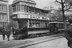 Double Decker London Tram Car has signs advertising Dewar's Whiskey & the Daily Mail Newspaper