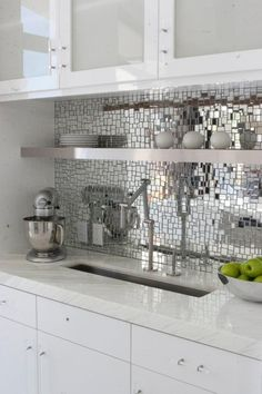 Mirrored Kitchen Backsplash. I like the collage look but I think I would paint my cabinets black to offset it :)