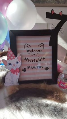 """This pink and white cat birthday party sign says """"Welcome to (name's) pawty. It also comes with a cat wearing a party hat to attach to the welcome sign."""