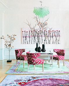 in the game room of Jeanine Lobell and Anthony Edwards Park Avenue apartment an aqua green and purple early 20th century Chinese Art Deco rug pulls together Art Deco chairs upholstered in a pink and white leaf patterned fabric and tree themed sculpture and painting. Image courtesy Elle Decor.