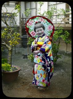 A girl standing in the yard with a sun shade, ca. 1920s by T.Enami