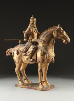 "A CHINESE TANG DYNASTY STYLE PARCEL GILT CARVED WOOD EQUESTRIAN WARRIOR GROUP, 20TH CENTURY, the warrior wearing traditional armor and holding a Guan Dao (polearm) in one hand and rope reigns in the other, while riding his saddled horse dressed with leather tack suspending whisks. Height: 23"" Width: 6 1/2"" Depth: 22"" Simpson Galleries $200"