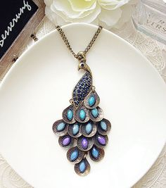 This is a beautiful antique gold peacock rhinestone necklace. The pendant measures 3 1/4 x 1 1/4, and the chain measures 24 around. The peacock- only ships to the us :-(
