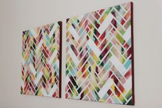 1) Paint whole canvas in different colors 2) Cut strips of painter's tape of the same size 3) Tape them onto the canvas in a herringbone pattern leaving some out 4) Spray paint whole canvas in white 5) Finish painting edges of canvas
