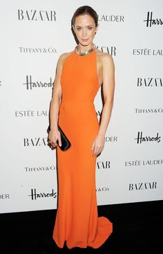 Emily Blunt in bold orange Alexander McQueen gown and 'Knuckle' clutch.