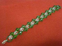 Bracciale di perle in cristallo trasparente e in cristallo verde bottiglia trasparente, con chiusura a moschettone argrntato.