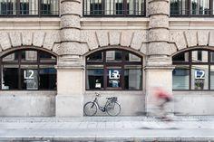 Das Foto entstand während eines Fotografie Workshops. Das Thema des Workshops war Langzeitbelichtung. Vor dem Fotograf Lippert in München fiel mir die gleichmäßige Architektur auf - Ich wartet auf einen Radfahrer, der die richtige Farbgebung mitbrachte und *klick* entstand das Foto.  München, Fotografie, Workshop, Lippert, Fahrrad, Streetfotografie, Fahrrad fahren