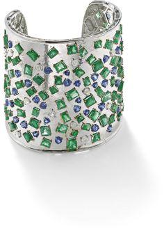 An emerald, sapphire and diamond cuff  Set throughout with step-cut emeralds, circular-cut sapphires and brilliant-cut diamonds, estimated diamond weight 4.70 carat, length 6.8 cm, inner diameter 6.2 cm