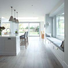 Una cocina blanca que aumenta su luminosidad y amplitud con la luz natural de sus grandes ventanales.