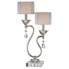 """Highlighted by 2 string drum shades and crystal-drop accents, this glamorous table lamp casts an elegant glow over your entryway table or nightstand.       Product: Table lamp    Construction Material: Crystal and metal    Color: Polished nickel    Features:  Twin door string shades Detailed with faceted tear drop crystal pendants    Accommodates: (2) 60 Watt bulbs - not included   Dimensions: 23.5"""" H x 12"""" W x 6"""" D"""