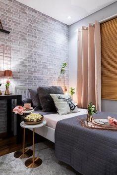 6. Quarto decorado em tons de cinza, rosa e cobre e papel de parede de tijolinhos.