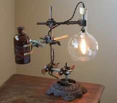 Industrial lamp with vintage amber bottle flower vase. Made with an antique oil lamp base and reclaimed laboratory equipment, including beautiful antique, ceramic glazed iron boss head clamps. Comes with a nostalgic Edison-style 25W candelabra bulb, cloth-covered wire and heavy duty
