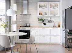 Cozinha em branco com eletrodomésticos em aço inoxidável, cadeiras brancas e mesa de refeição redonda