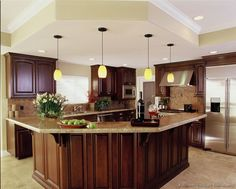 A Luxury Kitchen with Cherry Cabinets and a Large Angular Island Bar and matching soffit