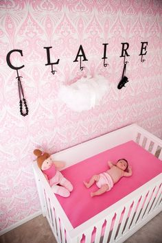Pretty pink wallpaper. Glam. Bold, solid color crib sheet. Love.