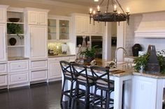 Elegant style informs this bold white kitchen, with near-black hardwood flooring. The massive granite-topped island features a built-in sink and space for three diners.