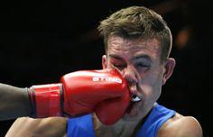 El galés Nathan Thorley recibe un golpe del mauriciano Kennedy St. Pierre durante su combate de boxeo de peso ligero masculino.