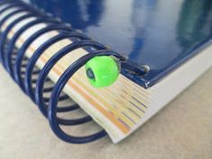 Hot glue a bead to the end of a spiral bound book