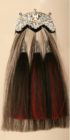 """Horse Hair Sporran worn by the pipers of the Royal Scots Dragoon Guards. Both the body and tassels are mingled horse hair. The regiment says: """"The late King George VI took a great interest in the Pipes and Drums, granted them the privilege of wearing the Royal Stuart tartan, and personally designed much of the uniform. The sporran is of grey horse hair reminiscent of the grey horses, with tassles of black and red hair similar to the jowl plumes which hung from the officers' bridles. """""""