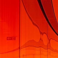 Bordje van de nooduitgang weerspiegeld in rode glazen wand van het regenboogpanorama in Aarhus, Denemarken