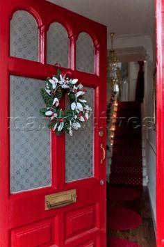 Open front door with Christmas garland in London home UK