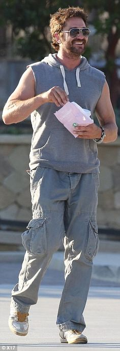 Comfy casual: The 300 actor wore a sleeveless grey hoodie with matching trousers, beige sn...