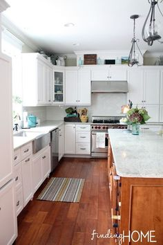 Elegant white kitchen. White painted cabinets with crackle white subway tile backsplash. Kashmire White granite countertops. Stainless steel farmhouse sink. Wide plank wood floors. Love the display shelf on top of the cabinets. From Finding Home.