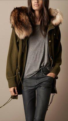 Green wool jacket with fox fur trim, grey t-shirt,black jeans.