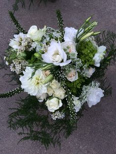Green and white bridal bouquet with freesia, roses, lisianthus, Queen Anne's lace, and dahlias with a plumosa cascade.
