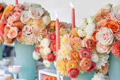 arranjo de flores em tons de coral com vasos azul claro e velas coral.
