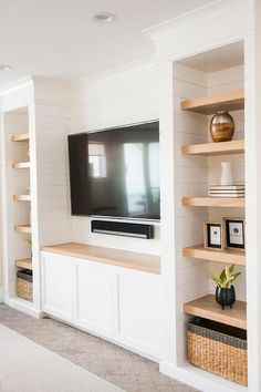 Well designed attic playroom features a flat panel television mounted to a white shiplap wall over white built in cabinets topped with a blond wood countertop.