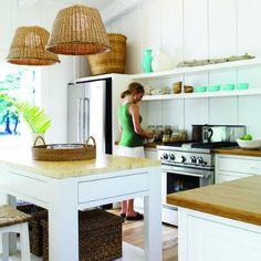 "The kitchen appears bigger than its 15-by-15 footprint thanks to its spare coastal palette of white paint ( Benjamin Moore ""Super White""), bamboo countertops ( Teragren), reclaimed barnwood flooring ( Black's Farmwood) and blue/cream ceramics ( Soulé Studio). Basket pendant lamps by Beach House Style highlight the kitchen island ( Woodenbridge, Inc.)."