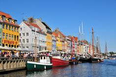 Busy summer day on Nyhavn Canal with colorful townhouses and wooden boats.