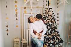 Picture of an affectionate couple next to their Christmas tree. Photo by usmfalina on Twenty20