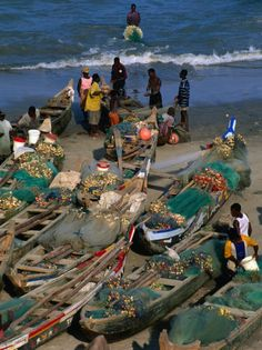 Traditional Fishing Pirogues on Cape Coast Beach Cape Coast Central Ghana. via posters.co.uk/Ghanaian-People
