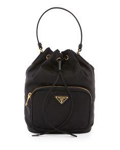 8bc8b2bf5751 Prada nylon bucket bag with calfskin trim. Golden hardware and tonal  topstitching. Front zip pocket with