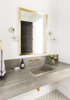 Gold and gray bathroom features a brass mirror, Bistro Polished Brass Mirror, lit by Schoolhouse Electric Orbit Sconces placed over a floating concrete washstand and sink fitted with a Kohler Purist Faucet alongside a gray cement tile floor, Encaustic Cement Tile Circulos Grey II.