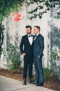 Smashbox studios same sex outdoor wedding with rustic decor groom black suit with white dress shirt and black bow tie with groom navy blue suit with white dress shirt and black bow tie